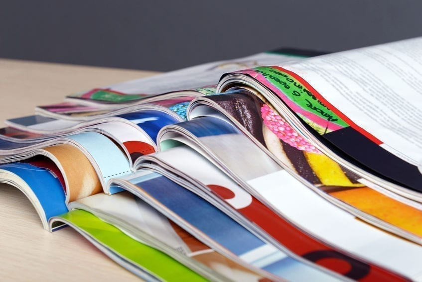Magazines on wooden table on gray background
